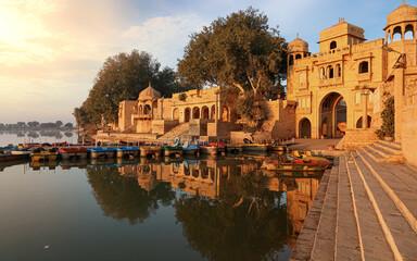 Wall Mural - Gadi Sagar (Gadisar) lake Jaisalmer Rajasthan India with tourist boats and ancient architecture at sunrise.