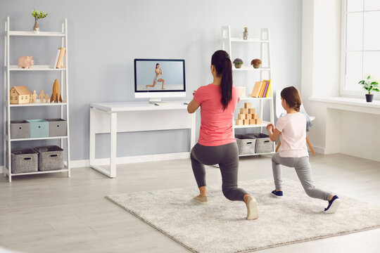 Family does exercises online. Mother and daughter watch online fitness trainer video course in room at home.