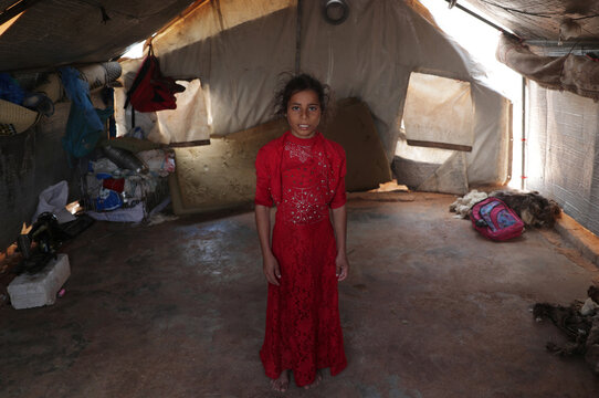 Displaced girl from Hama countryside, poses for a picture in a tent at Atmeh camp