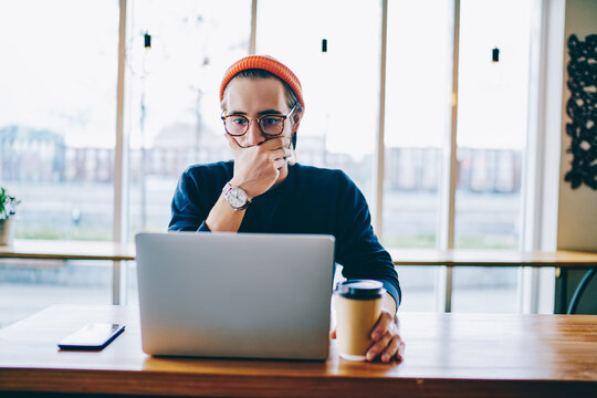 Emotional male freelancer shocked with software failure while using laptop computer in coworking space, amazed hipster guy reading news from social networks on netbook connected to wifi indoors.