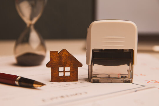 Businessman hands signing documents file paperwork financial or property mortgage real estate investment business on desk office with chart report document contact customer with wooden house models