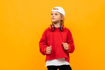 European blond boy in a red hoodie with red headphones with a white baseball cap on a yellow background