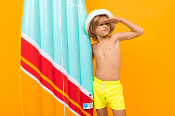 Handsome boy in swimming trunks holds a rubber mattress, smiles and gesticulates isolated on orange background