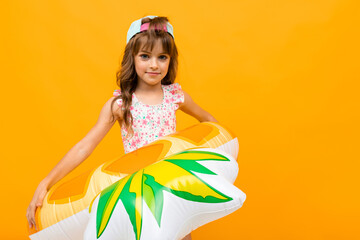 Beautiful little girl in swinsuit holds a rubber ring isolated on yellow and orange background