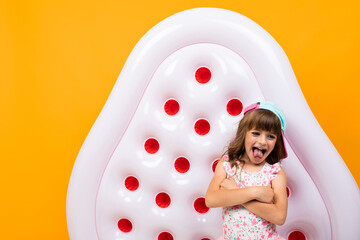 Beautiful little girl in swinsuit holds a rubber mattress and smiles isolated on yellow and orange background