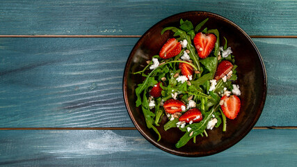 Spring salad with arugula, strawberries and ricotta. Food recipe background. space for text. top view.