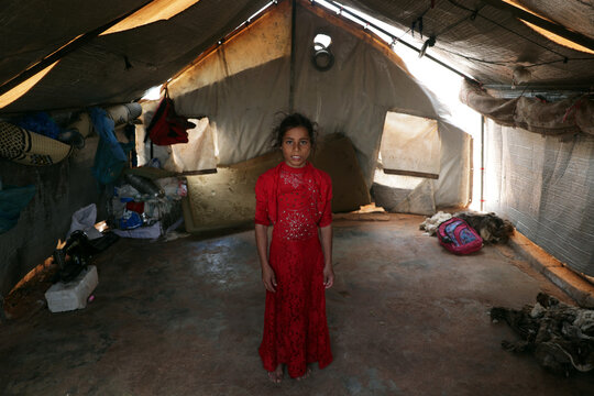 Ranim Barakat a 9-year-old Syrian displaced girl from Hama countryside, poses for a picture in a tent at Atmeh camp