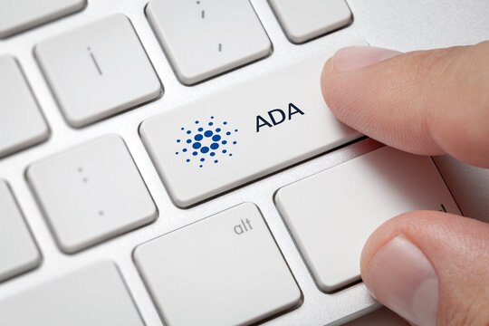 Macro of male hand pressing computer key with Cardano(ADA) currency symbol and text. Cryptocurrency and fast internet concept.