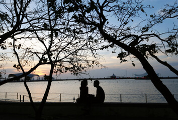 Silhouette of a couple wearing protective face masks is seen on the first day of reopening at the Ancol Beach amid the coronavirus disease (COVID-19) outbreak in Jakarta