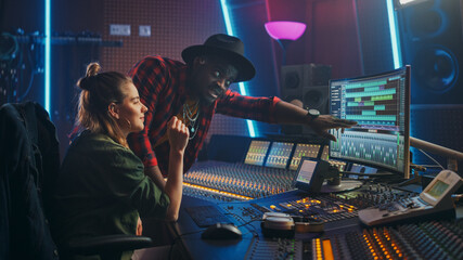 Producer and Professional Audio Engineer Working together in Music Recording Studio on a New Album,...