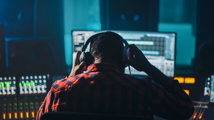 Fototapeta Stylish Artist, Musician, Audio Engineer, Producer Takes Place at His Control Desk in Music Record Studio, Uses Computer Screen show User Interface of DAW Software with Song Playing. Back View obraz