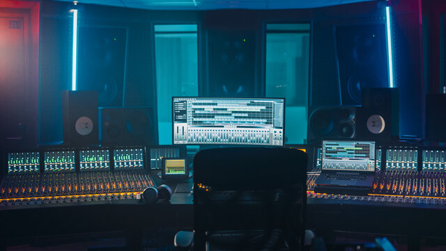 Shot of a Modern Music Record Studio Control Desk with Computer Screen show User Interface of DAW Software with Song Playing. Equalizer, Mixer and other Professional Equipment.