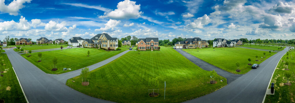 Large luxury real estate property sitting on more than an acre land with manicured lawn, long drive way on a new neighborhood street in Maryland
