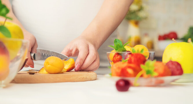 A pregnant woman eats fruit. Selective focus.