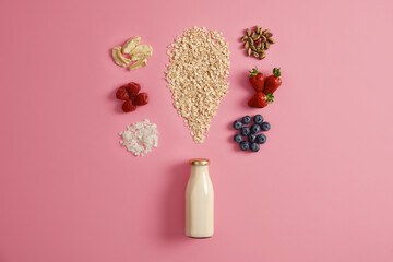 Uncooked oat with dried apples, coconut flakes, pistachio and appetizing ripe harvested fruits, bottle of fresh milk on rosy background. Healthy nutrition and breakfast. Delicious nutrient dessert Papier Peint
