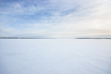 Frozen snow-covered lake under a clear blue sky with cirrus clouds. Fresh snow texture. Arctic,...