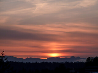 Sky with streaky clouds in a grayish and orange-red sky during sunrise over Cascade Range in Washington State.