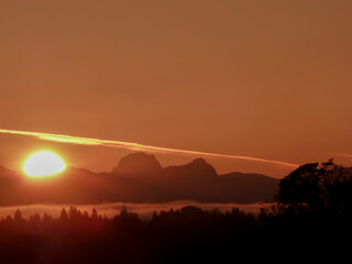 Large, bright sunlight and large contrail in an orange-red sky, and silhouette of the Cascade Range and forest in the foreground during sunrise on a spring day on Mercer Island in Washington State.