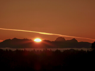 Bright sunlight and large contrail in an orange-red sky, and silhouette of the Cascade Range and forest in the foreground during sunrise on a spring day on Mercer Island in Washington State.