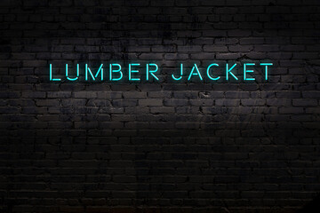 Night view of neon sign on brick wall with inscription lumber jacket