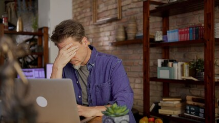 Mature man working alone from home. Sitting at desk teleworking with laptop in home office. Looking tired and troubled, thinking and having problem to solve.