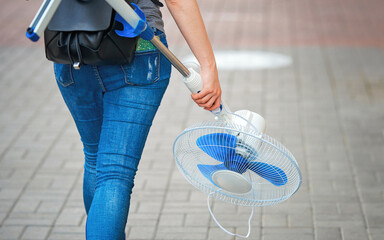 Girl carries in hand blower fan and walking on city street. Woman holding in hand standing fan. Abnormal heat, ventilation in office and home. Climate cooling and ventilation at home.