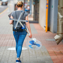 Woman holding in hand stand fan and walking on city street. Abnormal heat, ventilation in office and home.