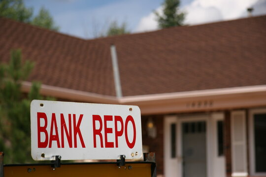 Bank Repo Sign on Home For Sale. The economy takes a turn for the worst with High Unemployment. Banks are repossessing homes when the owner can't pay the mortgage.