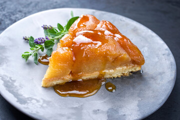 Traditional French tart tatin with apples and vanilla offered as close-up on a modern design plate with rustic background