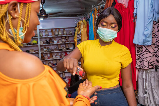 black woman who owns a boutique shop dispensing hand sanitizer for a customer