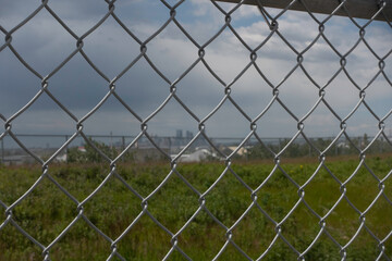 Chain Link Mesh Fence with calgary skyline in distance