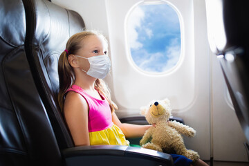 Aluminium Prints Equestrian Child in airplane in face mask. Virus outbreak.