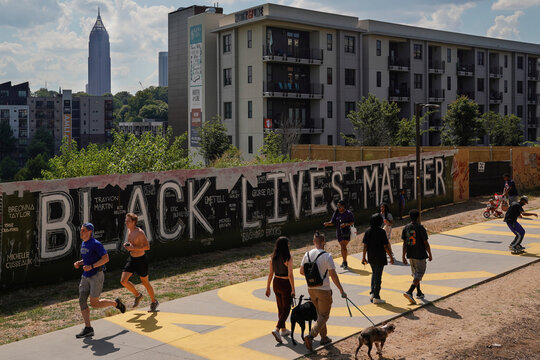 People pass a plywood wall with the 'Black Lives Matter' slogan on it, in Atlanta