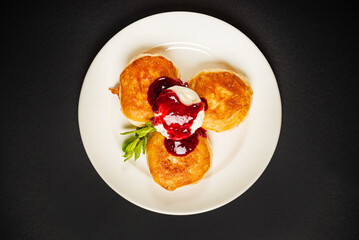 pancakes with berries sauce on black background