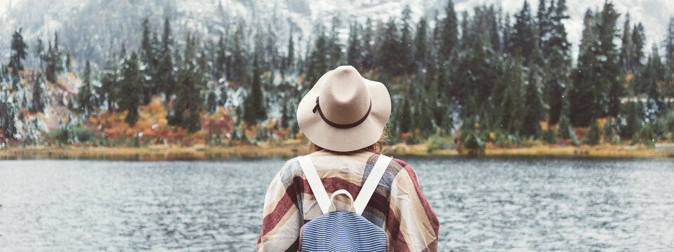 Adventure woman feeling happy among amazing mountains, enjoy the nature landsape. Forest and lake, wearing backpack, hat and poncho, boho and wanderlust style. Wide screen, panoramic
