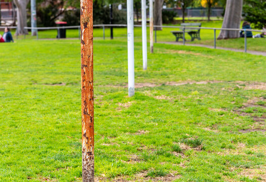 Four Australian football goal posts, one that is very rusted, at a suburban football oval in Brunswick East ,Melbourne, Australia