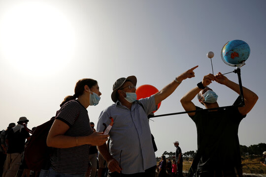 People stand next to a model of the earth, the moon and the sun as they gather to observe a partial solar eclipse from Mount Scopus in Jerusalem