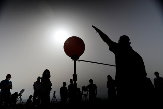 People stand next to a model of the earth, the moon and the sun as a partial solar eclipse is seen from Mount Scopus in Jerusalem