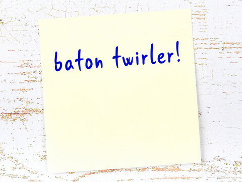 Yellow sticky note on wooden wall with handwritten word baton twirler