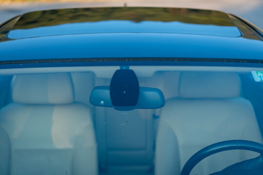 Windshield rain and light sensors position, luxury car windscreen, blue tinted glass, front view, technology design. Blue isolated glass  and dimming rear mirror