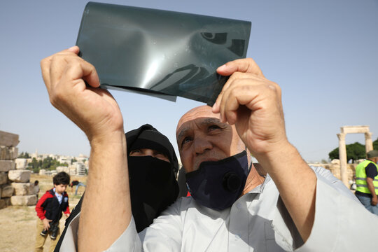 People use an X-ray film to observe a partial solar eclipse at the Amman Citadel, an ancient Roman landmark, in Amman