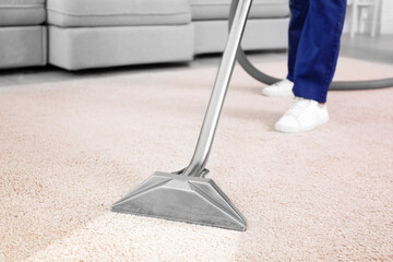 Worker removing dirt from carpet indoors, closeup. Cleaning service
