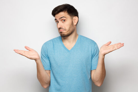 I don't know. Portrait of young confused man in blue t-shirt standing and shrugging shoulders, spreading hands isolated on gray background