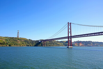 25 de Abril suspension Bridge connecting the city of Lisbon, to the municipality of Almada & the statue of Christ in the background over the Tejo Estuary, Lisbon, Portugal.