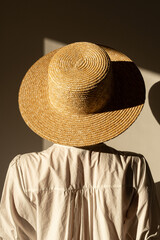 Young pretty woman in straw hat and white dress / sundress. Sunlight shadow on the wall. Minimal fashion design concept.