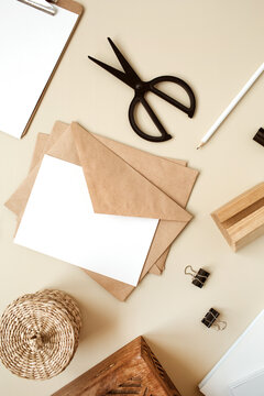 Blank paper sheet with envelope on beige table. Artist home office desk workspace with wooden casket, pencil and stationery. Webbing invitation card. Flat lay, top view mockup with empty copy space