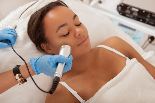 Relaxed African woman enjoying facial cosmetology treatment at beauty clinic