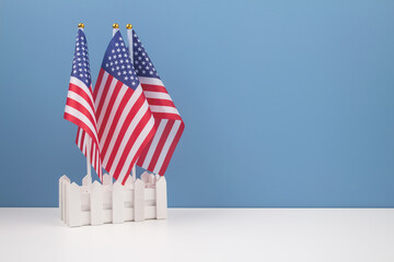 Creative composition with american flags on white table with blue wall background with copyspace for text. National symbol of USA - flag Old Glory. Flag Day or Independence Day celebration concept