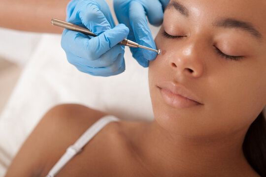 Cropped close up of a beautiful African woman getting facial skincare treatment at beauty salon