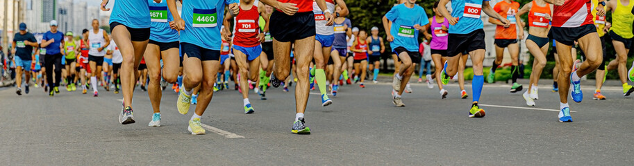 Fotomurales - large group of running athletes: men and women run city marathon